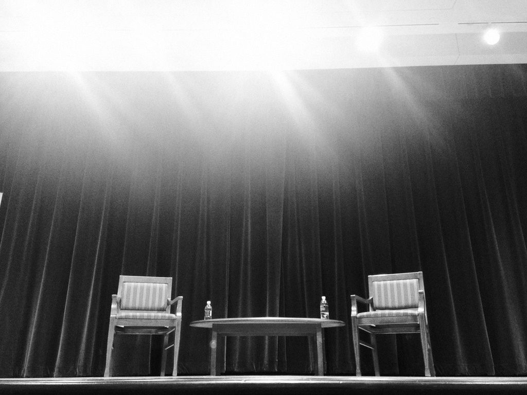 A light shining on empty stage with two chairs and a table