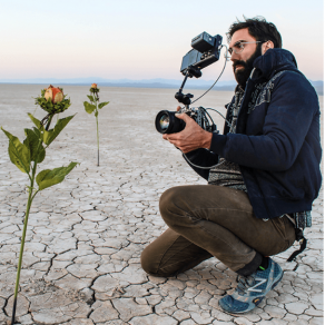 photo of bearded man kneeling with a camera, filming a rose in the desert