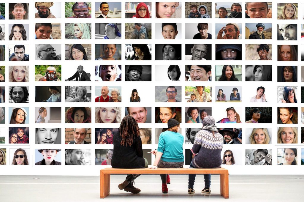 photoshopped image of three people sitting on a wooden bench facing a digital mural of photos of various people