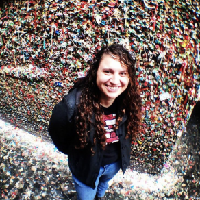 photo from above of woman with curly long brown hair in front of a wall of multicolored gum wads